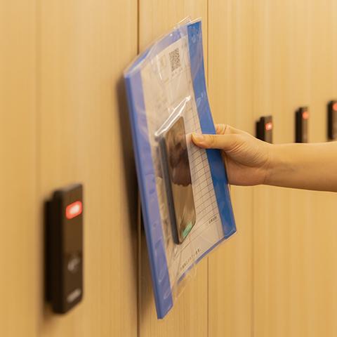 更衣室でお着替え後、専用スマートフォン入りカルテをかざし、ロッカーの鍵を閉める。